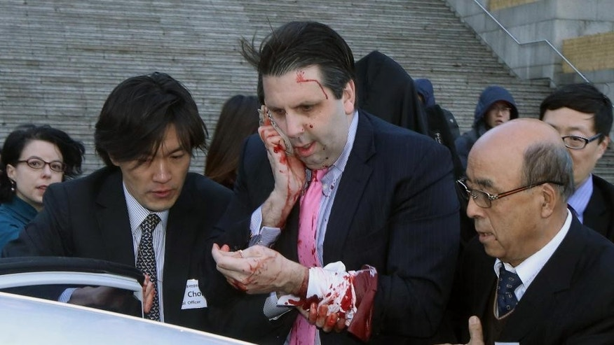 Injured U.S. Ambassador to South Korea Mark Lippert, center, gets into a car to leave for a hospital in Seoul, South Korea, Thursday, March 5, 2015. Lippert was attacked by a man wielding a razor and screaming that the rival Koreas should be unified, South Korean police and media said Thursday. His injuries weren't immediately clear and he was taken to a hospital for treatment. (AP Photo/Yonhap, Kim Ju-Sung)         KOREA OUT