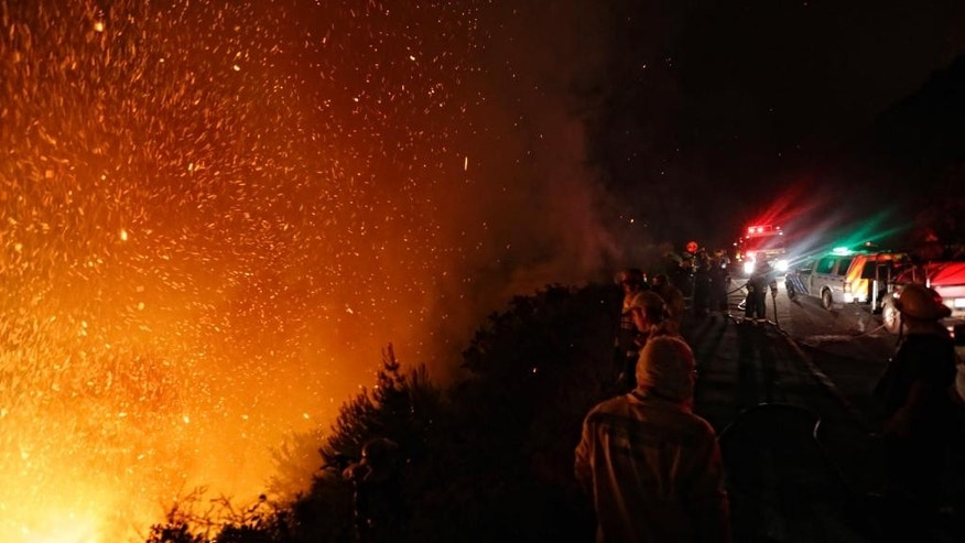 Firemen battle a blaze near Cape Town, South Africa. Wednesday March 4, 2015. A wildfire burned for a third day around Cape Town's Table Mountain on Tuesday. (AP Photo/Adrian de Kock)