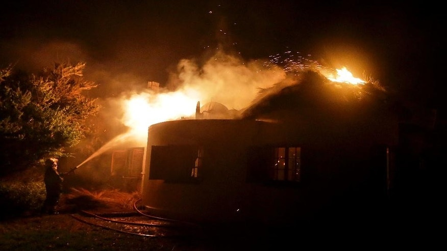 A fireman hoses down a burning house near Cape Town, South Africa Wednesday, March 4, 2015. A wildfire continues to burn across the city's southern peninsula after breaking out Sunday with firefighting re-enforcement being flown in to assist fighting the blaze.  (AP Photo/Adrian de Kock)