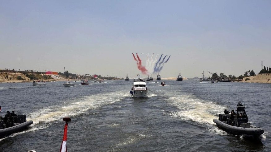 FILE - In this Aug. 5, 2014 file image released by the Egyptian Presidency, warplanes fly overhead during a ceremony broadcast on state television to inaugurate the start of a new segment of the Suez Canal, in the canal city of Ismailia, Egypt. Egypt's Suez Canal Authority is in a race to quickly expand the vital waterway for two-way traffic by August 2015. President Abdel-Fattah el-Sissi has made the project a point of nationalist glory, not to mention a cornerstone of plans to revive the economy. The canal was opened for navigation in 1869. (AP Photo/Egyptian Presidency, File)