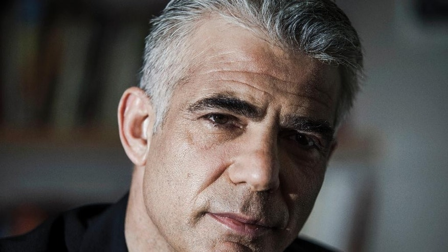 In this Wednesday, March 4, 2015 photo, Yair Lapid, leader of the Israeli political party Yesh Atid, listens during an  interview with The Associated Press in Tel Aviv, Israel. Bruised by a rough term as finance minister, the former TV anchorman and one-time boxer is now mounting a furious late-round comeback with a message linking prosperity with regional peace. (AP Photo/Dan Balilty)