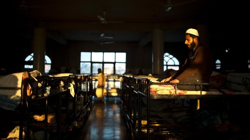 In this Tuesday, Jan. 27, 2015 photo, a Pakistani student of a madrassa, or Islamic school, sits on his bed rehearsing for his exam at the seminary dorms on the outskirts of Islamabad, Pakistan. There's no exact number of madrassas in Pakistan but estimates put the number in the tens of thousands. They provide food, housing and a religious education to students from around the country. (AP Photo/Muhammed Muheisen)