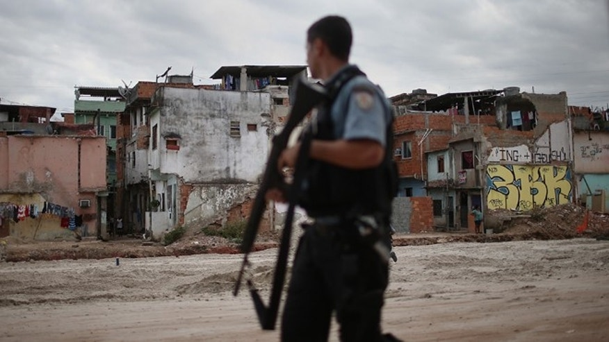 RIO DE JANEIRO, BRAZIL - MAY 27:  A police officer patrols past an area where homes were torn down in the Manguinhos community on May 27, 2014 in Rio de Janiero, Brazil. Residents from one section of the 'favela', visited by Pope Francis in July 2013, have been affected by construction from the improvement works project begun in 2008. A full sanitation system has yet to be built. Evictions and demolitions have been occurring in Rio favelas ahead of the 2014 FIFA World Cup and Rio 2016 Olympic Games in spite of a housing shortage in the city. Rio's housing and urban planning goals include a planned five percent reduction of areas occupied by favelas by 2016. Alternative affordable housing, generally on the peripheries of the city, is unable to meet demand and some residents complain they have not received adequate compensation for demolished homes.  (Photo by Mario Tama/Getty Images)
