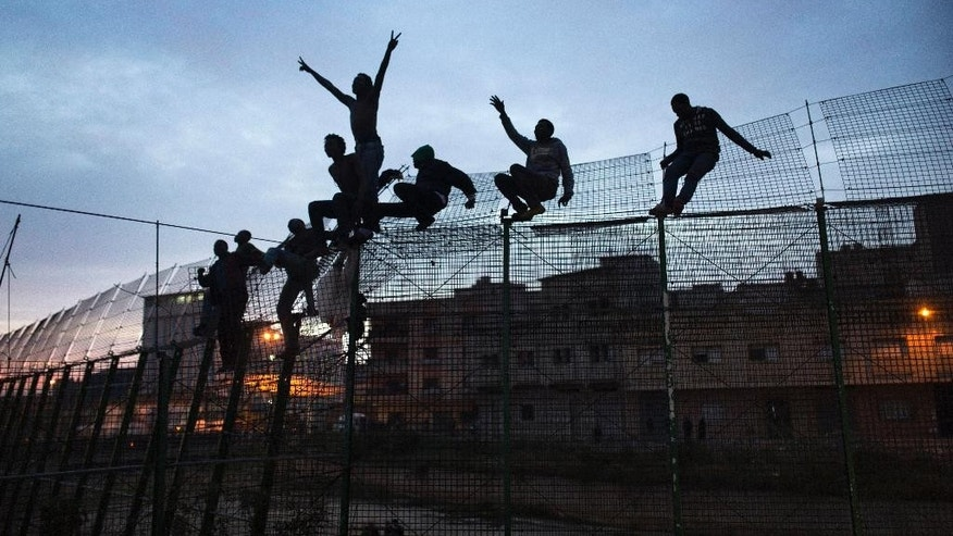 March 28, 2014: In this file photo, Sub-Saharan migrants climb over a metallic fence that divides Morocco and the Spanish enclave of Melilla. (AP)