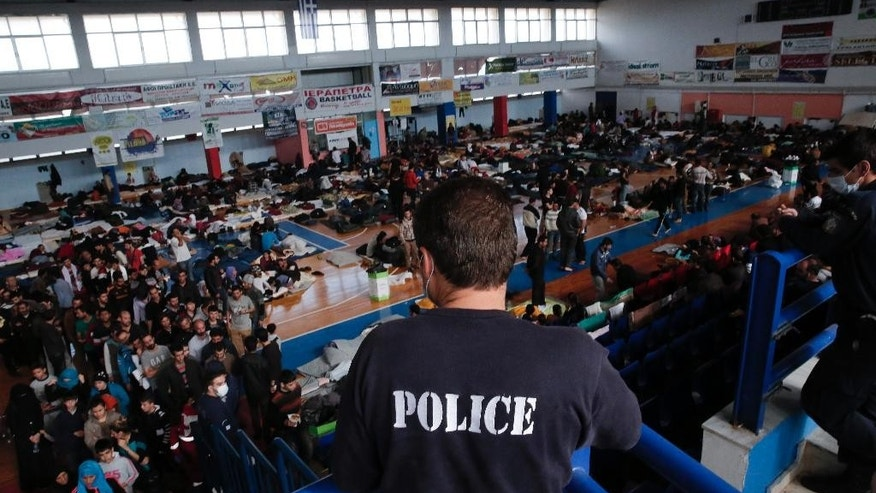 Nov. 28, 2014: In this file photo, a policeman observes the scene as immigrants who arrived aboard a cargo ship from Turkey queue for meals while others sit on bedding in a basketball arena where they have been given temporary shelter in the town of Ierapetra, on the southern Greek island of Crete. (AP)