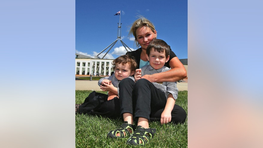 Danica Weeks, who lost her husband on Malaysia Airlines Flight 370, poses for a photo with her sons Lincoln, 4,  front right and Jack,1, outside the Australia Parliament House in Canberra, Australia, Thursday, March 5, 2015. Weeks and her two sons are in Canberra to meet prime minister Tony Abbott and attend a briefing with officials about the ongoing search efforts for the plane that has been missing since March 8, 2014.(AP Photo/Rob Griffith)