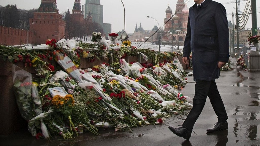 Italian Prime Minister Matteo Renzi walks to pay his respects at the place where Boris Nemtsov, a charismatic Russian opposition leader and sharp critic of President Vladimir Putin, was gunned down on Feb. 27, near the Kremlin in Moscow, Russia, Thursday, March 5, 2015. The Kremlin Wall and St. Basil's Cathedral are seen in the background. (AP Photo/Alexander Zemlianichenko)