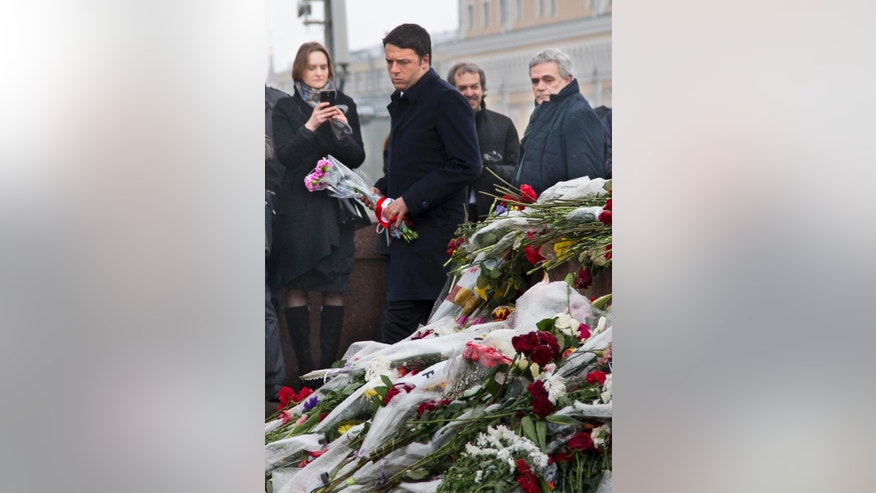 Italian Prime Minister Matteo Renzi pay respects at the place where Boris Nemtsov, a charismatic Russian opposition leader and sharp critic of Russian President Vladimir Putin, was gunned down on Friday, Feb. 27, 2015 near the Kremlin in Moscow, Russia, Thursday, March 5, 2015. (AP Photo/Alexander Zemlianichenko)