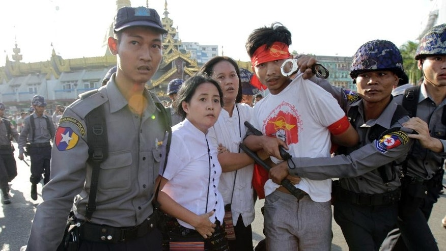 Protesters are detained by police after a gathering opposing a new education law in Yangon, Myanmar, Thursday, March 5, 2015. Police cracked down on students and other activists opposing Myanmar's new education law, charging protesters with batons and dragging them into trucks at the landmark Sule Pagoda in the heart of the old capital, Yangon. (AP Photo/Khin Maung Win)