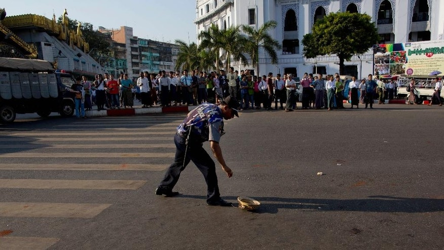 A police officer collects a traditional Burmese headwear belongs to a student protester after detaining them during a protest march in Yangon, Myanmar, Thursday, March 5, 2015. Police cracked down on students and other activists opposing Myanmar's new education law, charging protesters with batons and dragging them into trucks at a landmark pagoda in the heart of the old capital, Yangon. (AP Photo/Gemunu Amarasinghe)