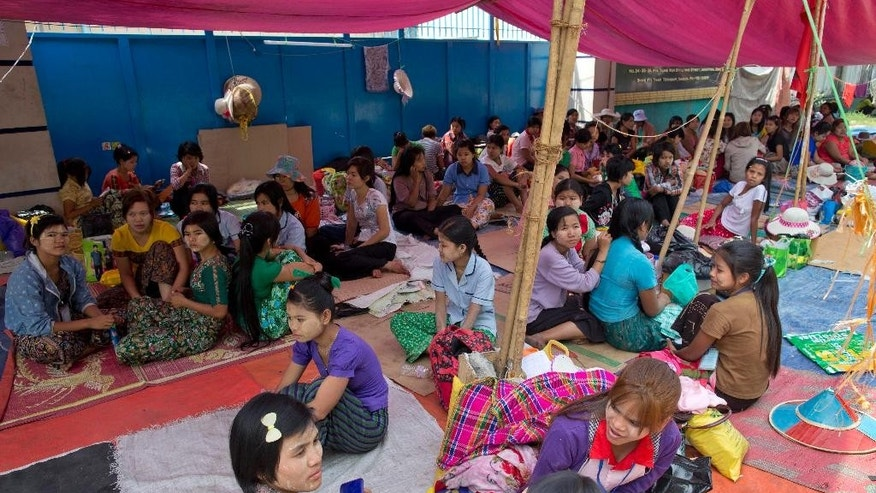 In this Feb 19, 2015 photo, Myanmar workers of Korean-owned Costec garment factory stage a sit-in protest under a makeshift tent camp outside the entrance to the factory in Shwepyithar, suburbs of Yangon, Myanmar. Police have detained more than a dozen factory workers, when about 100 workers tried to march from their factories into downtown Yangon late Wednesday demanding higher wages and better working conditions after negotiations between factory owners, labor union representatives, employees and government officials were at a standstill, with the authorities threatening a crackdown if the workers don't give up their protest. (AP Photo/Gemunu Amarasinghe)