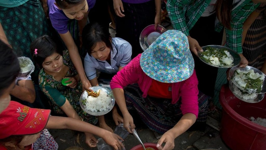 In this Feb 19, 2015 photo, Myanmar workers of Korean-owned Costec garment factory gather to collect a meal during a protest outside the entrance to the factory in Shwepyithar, suburbs of Yangon, Myanmar. Police have detained more than a dozen factory workers, when about 100 workers tried to march from their factories into downtown Yangon late Wednesday, March 4, 2015 demanding higher wages and better working conditions after Negotiations between factory owners, labor union representatives, employees and government officials were at a standstill, with the authorities threatening a crackdown if the workers don't give up their protest. (AP Photo/Gemunu Amarasinghe)