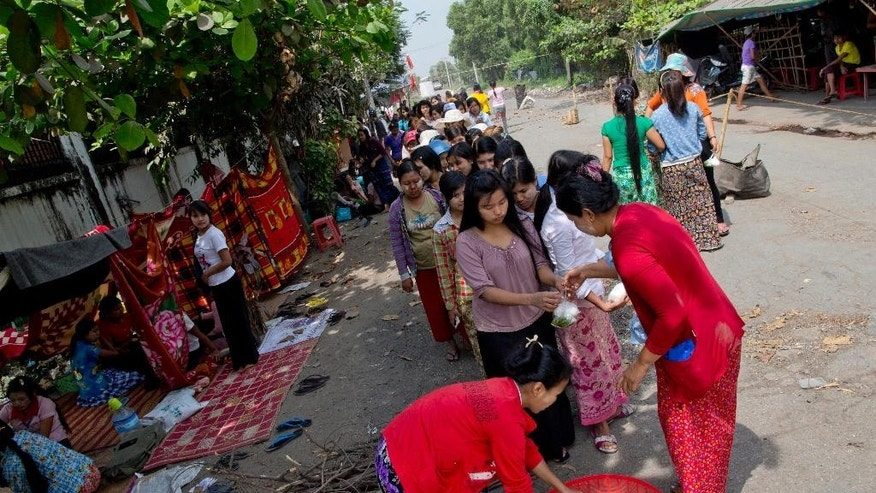 In this Feb. 19, 2015 photo, Myanmar workers of Korean-owned Costec garment factory stand in a line to collect a meal during a protest outside the entrance to the factory in Shwepyithar, suburbs of Yangon, Myanmar. Police detained more than a dozen factory workers, when about 100 workers tried to march from their factories into downtown Yangon late Wednesday, March 4, 2015 demanding higher wages and better working conditions after Negotiations between factory owners, labor union representatives, employees and government officials were at a standstill, with the authorities threatening a crackdown if the workers don't give up their protest. (AP Photo/Gemunu Amarasinghe)
