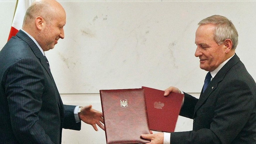 Oleksandr Turchynov, chairman of the Ukrainian Security and Defense Council, left, and head of Poland's National Security Office, Stanislaw Koziej, right, exchange documents they signed agreeing on a cooperation between their offices, in Warsaw, Poland, Thursday, March 5, 2015. They also held talks concerning the situation in Ukraine and cooperation in the security and defense areas. (AP Photo/Czarek Sokolowski)