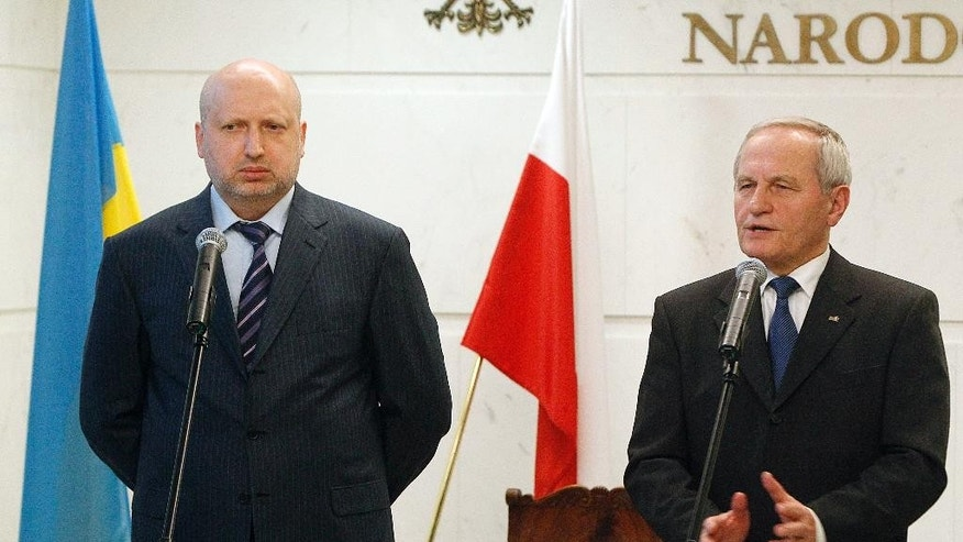 Oleksandr Turchynov, chairman of the Ukrainian Security and Defense Council, left, and head of Poland's National Security Office Stanislaw Koziej, right, talk to reporters before holding a meeting in Warsaw, Poland, Thursday, March 5, 2015, in which they discussed situation in Ukraine and cooperation in the security and defense areas. (AP Photo/Czarek Sokolowski)