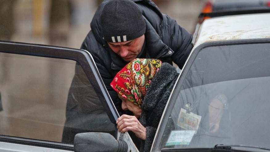 In this picture taken on March 3, 2015, an elderly woman is helped out of a car outside a bank in the town of Kurakhove, Ukraine, just a few miles away from the area controlled by Russia-backed rebels. Restrictions imposed on travel from separatist-controlled areas to the rest of Ukraine, coupled with a recent surge in reports of supply trucks being blocked from sending goods to the separatist zone, underscore the vulnerability of the Russia-backed rebel rule as well as the Ukrainian government's virtual crackdown on its own citizens. (AP Photo/Vadim Ghirda)