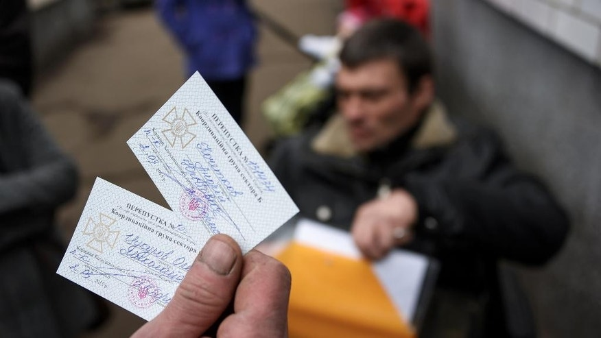 In a picture taken on March 2, 2015, a man holds permits to cross from Ukraine to rebel held territory in the town of Velyka Novosilka, Ukraine. Restrictions imposed on travel from separatist-controlled areas to the rest of Ukraine, coupled with a recent surge in reports of supply trucks being blocked from sending goods to the separatist zone, underscore the vulnerability of the Russia-backed rebel rule as well as the Ukrainian government's virtual crackdown on its own citizens. (AP Photo/Mstyslav Chernov)
