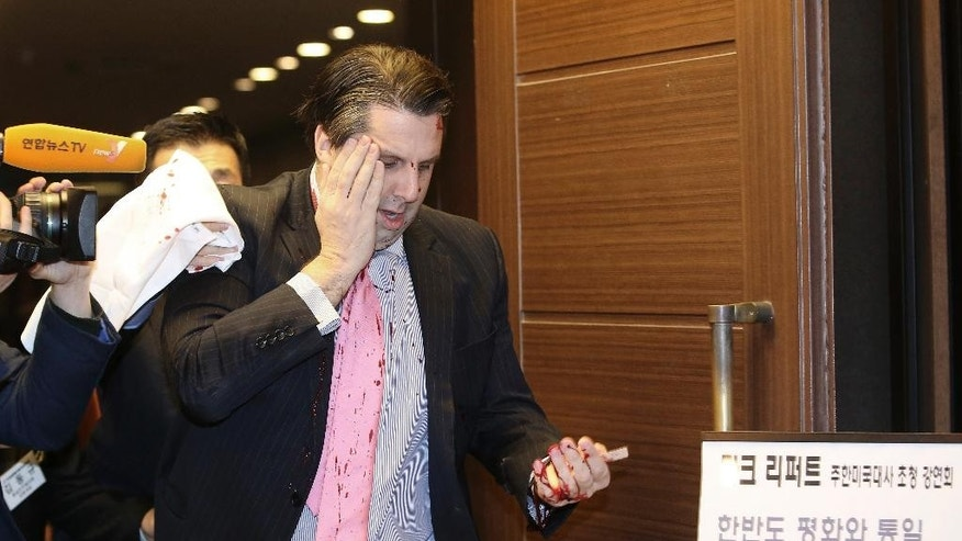 "U.S. Ambassador to South Korea Mark Lippert placing his right hand on his face leaves a lecture hall for a hospital in Seoul, South Korea, Thursday, March 5, 2015 after being attacked by a man. Lippert was in stable condition after the man screaming demands for a unified North and South Korea slashed him on the face and wrist with a knife, South Korean police and U.S. officials said. The board at right reads: ""U.S. Ambassador to South Korea Mark Lippert's lecture."" (AP Photo/Yonhap, Kim Ju-sung)  KOREA OUT"
