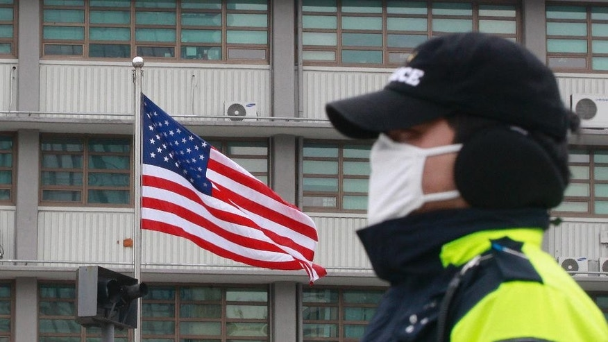 A South Korean police officer stands guard near the U.S. Embassy in Seoul, South Korea, Thursday, March 5, 2015. U.S. Ambassador Mark Lippert was in stable condition after a man screaming demands for a unified North and South Korea slashed him on the face and wrist with a knife, South Korean police and U.S. officials said Thursday. (AP Photo/Ahn Young-joon)