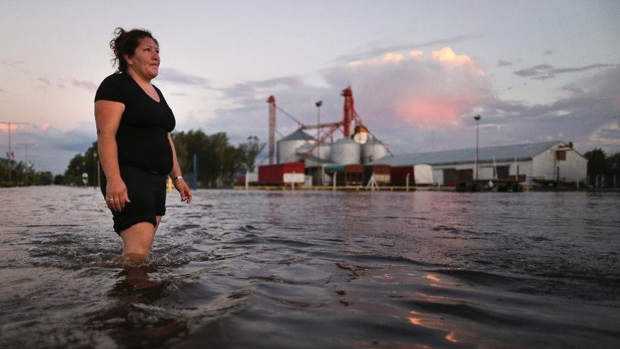 A woman walks in knee-high flood waters in Idiazabal, Argentina, Thursday, March 5, 2015. Flooding throughout four Argentine provinces have forced thousands of people to flee their homes. In the small town of Idiazabal, in the Cordoba province, residents continue to wade through fully submerged streets that have been under water for over one week. While rains stopped on Thursday and are not expected to return over the coming days, floodwaters have not subsided. (AP Photo/Nico Aguilera)
