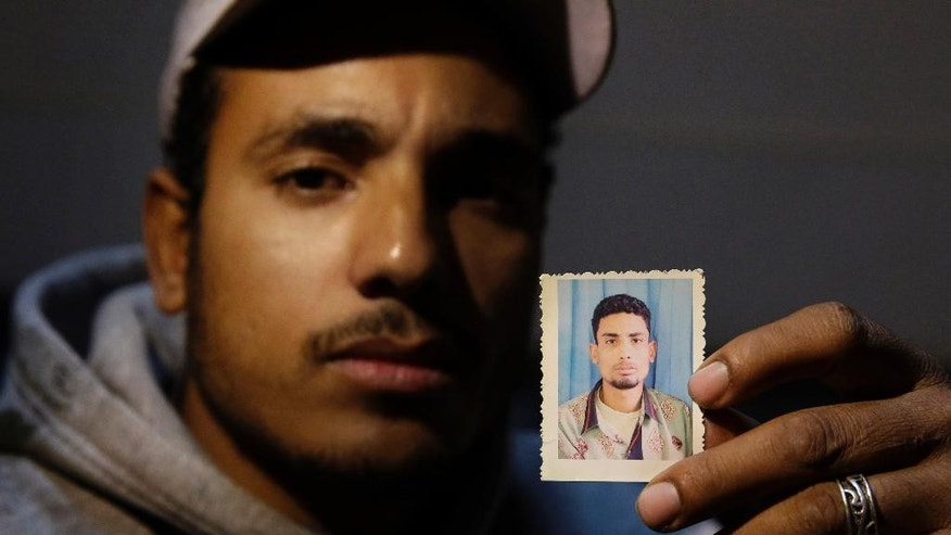 In this Wednesday, Feb. 25, 2015 photo, Ragab Farghali, 28, holds the photo of his 30-year-old brother, Walid Farghali, who was killed by an Egyptian policeman, during an interview with the Associated Press in Cairo, Egypt.  A 30-year-old minibus driver, Walid Farghali was shot in the chest by a policeman on Feb. 1 after he tried to get away when asked for his driver's license. (AP Photo/Hassan Ammar)