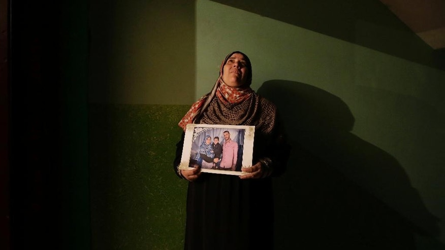 In this Wednesday, Feb. 25, 2015 photo, Hayam Salama, mother of Mohammed Ahmed, who was killed by an Egyptian policeman, poses for a portrait with her son's picture during an interview with the Associated Press in Cairo, Egypt. Mohammed Ahmed, a 19-year-old arrested and detained for trying to blow up a government building and over accusations of belonging to the Muslim Brotherhood, lay injured in a hospital bed when he allegedly argued with a policeman on Feb. 1. The policeman shot him seven times. (AP Photo/Hassan Ammar)
