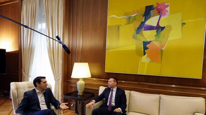 "Greece's Prime Minister Alexis Tsipras, left, speaks with Governor of the Bank of Greece Yannis Stournaras at Maximos Mansion in Athens, Friday, March 6, 2015. European Central Bank head Mario Draghi said the ECB ""stood ready"" to once again permit Greek banks to use junk-rated Greek government bonds as collateral to get credit from the ECB. That would happen as soon as the bank assesses that Greece is likely to successfully complete a creditor review of its progress. (AP Photo/Thanassis Stavrakis)"
