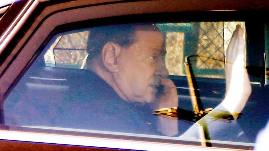 Italy's former Premier Silvio Berlusconi speaks on a mobile phone as he leaves the 'Sacra Famiglia' institute in Cesano Boscone, near Milan, Italy, Friday, March 6, 2015. (AP Photo/Luca Bruno)