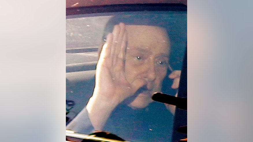 RESENDING TO PROVIDE AN ALTERNATIVE CROP OF XLB102 - Italy's former Premier Silvio Berlusconi waves as he leaves the 'Sacra Famiglia' institute in Cesano Boscone, near Milan, Italy, Friday, March 6, 2015. (AP Photo/Luca Bruno)