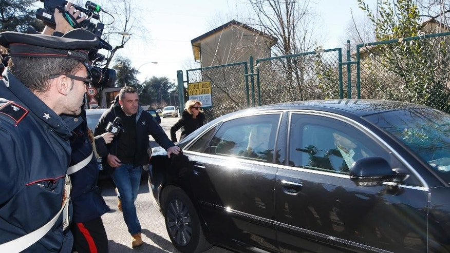 Italy's former Premier Silvio Berlusconi waves as he leaves the 'Sacra Famiglia' institute in Cesano Boscone, near Milan, Italy, Friday, March 6, 2015. (AP Photo/Luca Bruno)