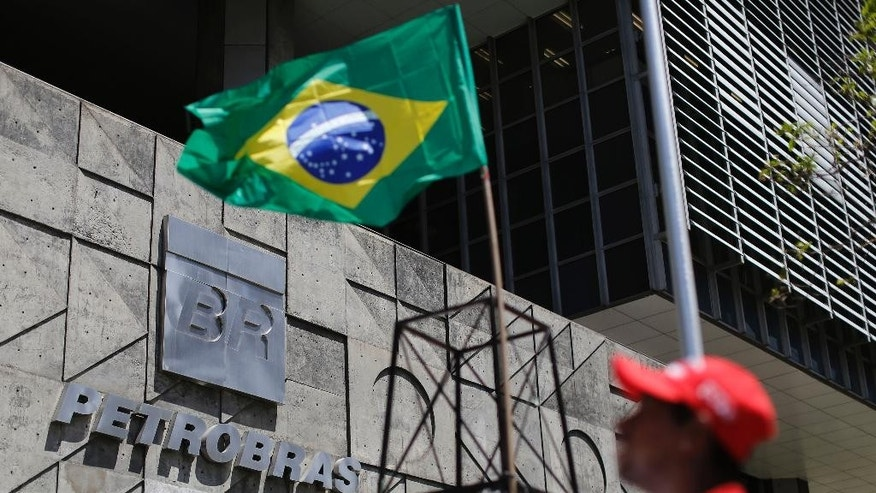 A metallurgical union worker stands outside the state-run oil company Petrobras during a protest for better labor conditions and against layoffs, in Rio de Janeiro, Brazil, Wednesday, March 4, 2015. The company has been engulfed in an ever-sprawling corruption scandal, a kickback scheme that prosecutors say is the largest ever uncovered in Brazil. (AP Photo/Leo Correa)