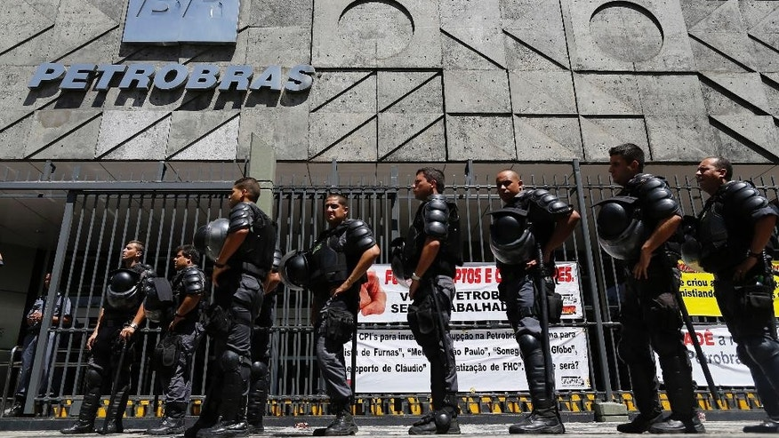 Riot police officers stand guard during a protest of metallurgical union workers demanding better labor conditions and against layoffs at the state-run oil company Petrobras, in Rio de Janeiro, Brazil, Wednesday, March 4, 2015. The company has been engulfed in an ever-sprawling corruption scandal, a kickback scheme that prosecutors say is the largest ever uncovered in Brazil. (AP Photo/Leo Correa)