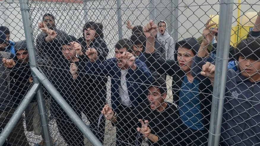 In this Saturday, Feb. 14, 2015, file photo migrants shout behind an iron fence at the Foreigners Detention Center in Amygdaleza, Greece, north of the capital Athens, following the apparent suicide of a Pakistani detainee. European Union countries are immersed in a full-fledged migration crisis. With the EU lacking funds and resources, some officials are even floating the idea of a multinational border guard to deal with arrivals of hundreds of thousands from war-torn countries like Syria, poor African nations and non EU neighbors like Kosovo. (AP Photo/ InTime News/Nikos Halkiopoulos, File) GREECE OUT