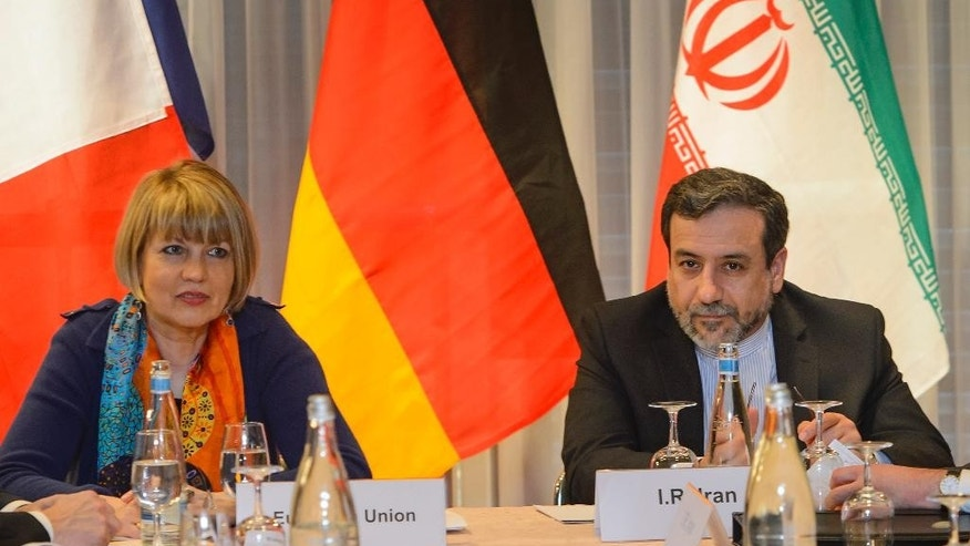 The European Union's political director Helga Schmid, left, sits next to Iranian senior nuclear negotiator Abbas Araqchi, right, during nuclear talks on Iran between the EU, France, Germany, Britain, China, Russia, the US and Iran in Montreux, Switzerland, Thursday, March 5, 2015. (AP Photo/Keystone, Jean-Christophe Bott)