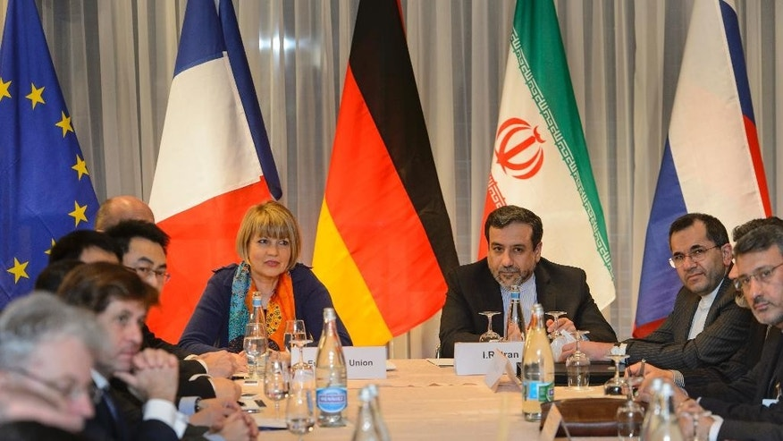 The European Union's political director Helga Schmid, center left, sits next to Iranian senior nuclear negotiator Abbas Araqchi, center right, during nuclear talks on Iran between the EU, France, Germany, Britain, China, Russia, the US and Iran in Montreux, Switzerland, Thursday, March 5, 2015. (AP Photo/Keystone, Jean-Christophe Bott)