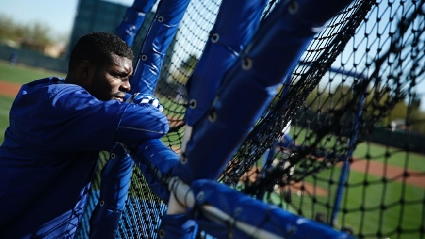 Los Angeles Dodgers' Yasiel Puig watches a batter hit during a spring training baseball workout Wednesday, Feb. 25, 2015, in Phoenix. (AP Photo/John Locher)
