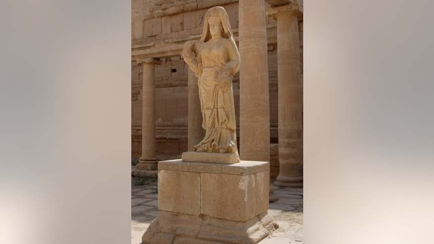 FILE - In this file photo taken July 27, 2005, the statue of a robed woman, believed to be the spouse of a former king, stares down at visitors in the ruins of the ancient city of Hatra, 320 kilometers (200 miles) north of Baghdad, Iraq. Islamic State militants control the 2,300-year-old city of Hatra, a well preserved complex of temples south of Mosul and a UNESCO World Heritage site. (AP Photo/Antonio Castaneda, File)
