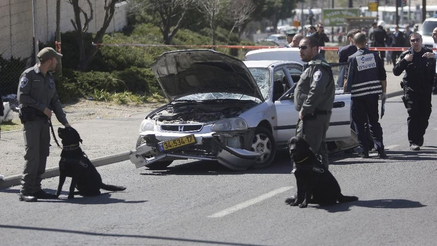 Israeli police stand next to a car at the scene of an of an apparent attack in Jerusalem, Friday, March 6, 2015. Israeli police say a suspected Palestinian motorist has rammed his car into five people near a Jerusalem police station, injuring five, before he was shot and wounded by a security guard. (AP Photo/Sebastian Scheiner)