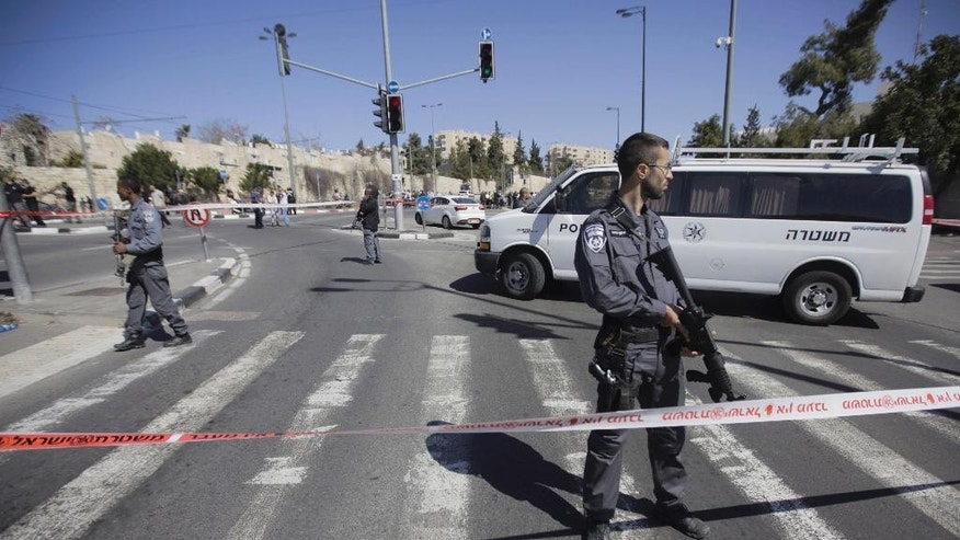 Israeli police stand at the scene of an of an apparent attack in Jerusalem, Friday, March 6, 2015. Israeli police say a suspected Palestinian motorist has rammed his car into five people near a Jerusalem police station, injuring five, before he was shot and wounded by a security guard.(AP Photo/Sebastian Scheiner)
