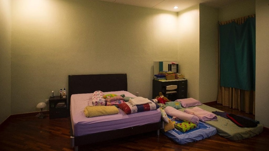 "This Saturday, Feb. 28, 2015, photo, shows the master bedroom of Foong Wai Yueng, 40, a stewardess who was aboard Malaysian Airlines flight 370 when it disappeared last March, in Kuala Lumpur, Malaysia. Yueng's husband, Lee Khim Fatt, 45, says  ""I have not changed or moved anything except changing the sheets, as the kids have always slept with us here. But ever since that day, I sleep on the floor mattress with my son. It doesn't feel the same, doesn't feel right sleeping on the mattress without her beside me."" (AP Photo/Joshua Paul)"