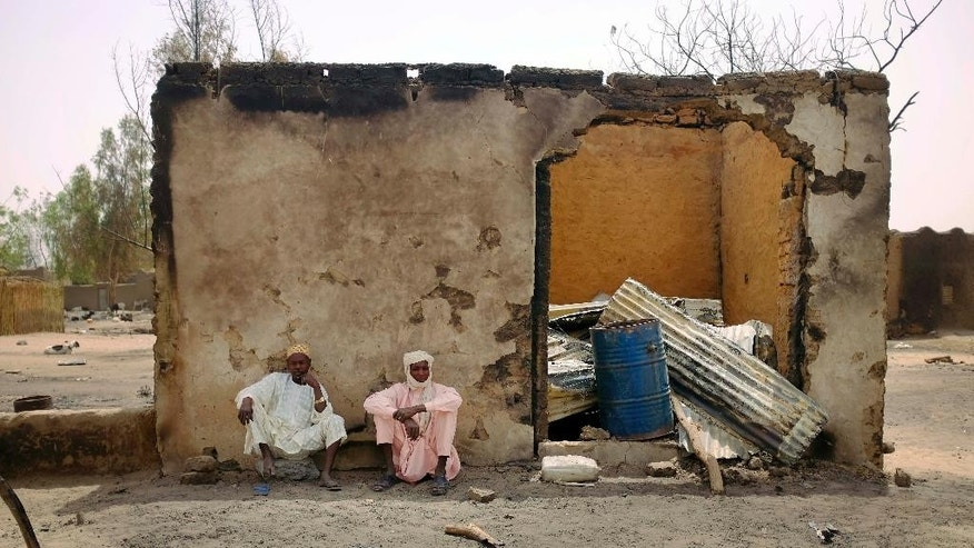 Two Chadian men sit by a burned store, in the Lake Chad shore village of N'Gouboua, Chad, Thursday, March 5, 2015. Boko Haram militants arrived in N'gouboua before dawn on Feb. 13, marking the first attack of its kind on Chad. By the time the scorched-earth attack ended, they had burned scores of mud-brick houses by torching them with gasoline and had killed at least eight civilians and two security officers. Some 3,400 Nigerian refugees had been living in the village at the time of the attack, and all have since been relocated further inland. (AP Photo/Jerome Delay)