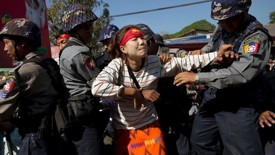 A student protester scuffles with police officers by a truck in Letpadan, north of Yangon, Myanmar Friday, March 6, 2015. Police cracked down on student protesters opposing Myanmar's new education law Friday, roughly grabbing demonstrators and loading them onto trucks in the third such clampdown in as many days. (AP Photo/Gemunu Amarasinghe)