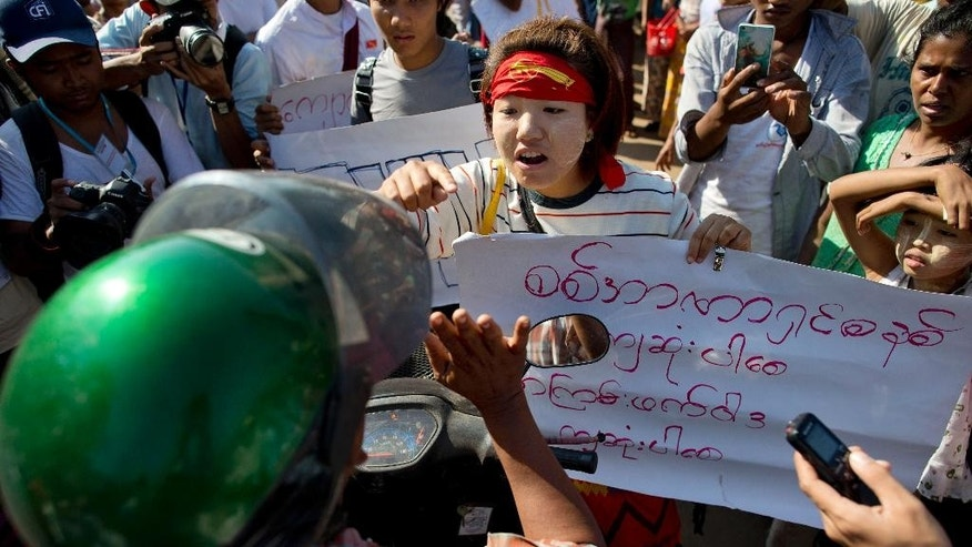 A student protester confronts a man in plain clothes during a protest in Letpadan, north of Yangon, Myanmar, Friday, March 6, 2015. Police cracked down on student protesters opposing Myanmar's new education law Friday, roughly grabbing demonstrators and loading them onto trucks in the third such clampdown in as many days. (AP Photo/Gemunu Amarasinghe)