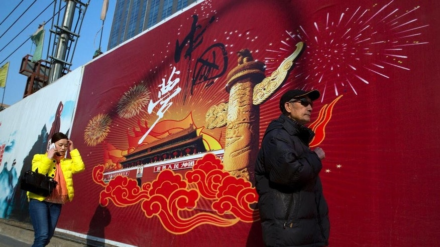 "In this March 5, 2015 photo, residents pass by a billboard with the words ""China Dream"" in Beijing. Chinese President Xi Jinping's trademark ""China Dream of the Great Rejuvenation of the Chinese Nation"" and the ""Four Comprehensives"" that followed are just the latest examples of the slogans exhortations and statements of intent that are a mainstay of Chinese political life. (AP Photo/Ng Han Guan)"