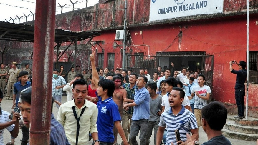 In this Thursday, March 5, 2015 photo, members of a mob pull a man, centre with blooded face, accused of rape, out of the Central Jail where he was held in Dimapur, in the northeastern Indian state of Nagaland. Several thousand people overpowered security at Dimapur Central Prison in Nagaland on Thursday, and seized the rape suspect, whom they also accused of being an illegal migrant from Bangladesh. They pelted him with stones and beat him to death, said police Constable Sunep Aier. (AP Photo)
