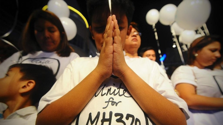 FILE - In this March 18, 2014, photo, a young Malaysian boy prays at an event for the missing Malaysia Airlines Flight 370 at a shopping mall in Petaling Jaya, on the outskirts of Kuala Lumpur, Malaysia. For centuries, human beings have clambered aboard vessels and sailed past the horizon, unsure whether they would return. Sometimes they didn't. Today, the world is a year into the vexing disappearance of an enormous jetliner without any sort of resolution, a mystery more enduring than the rest. (AP Photo/Joshua Paul, File)