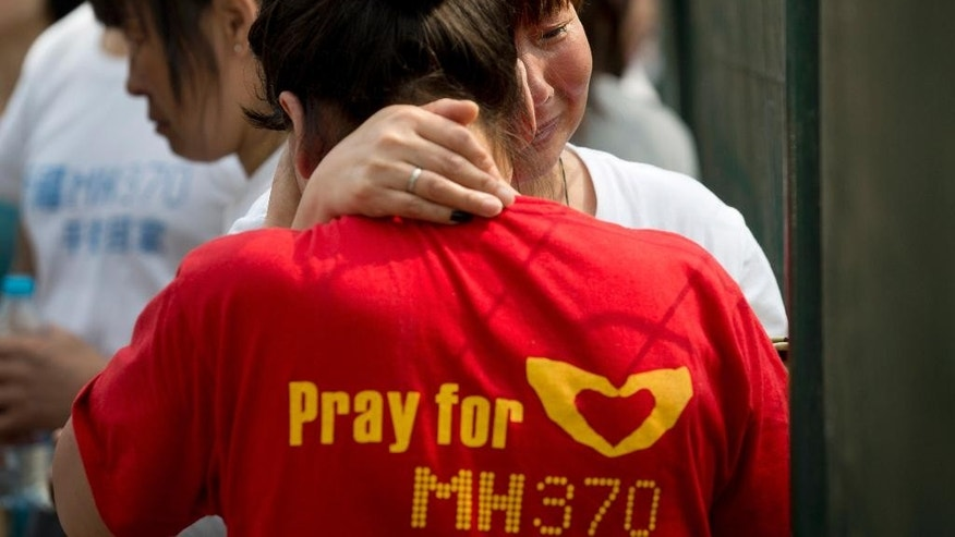 FILE - In this April 25, 2014, photo, Chinese relatives of passengers onboard the Malaysia Airlines MH370 cry during a protest at the Malaysian embassy in Beijing, China. For centuries, human beings have clambered aboard vessels and sailed past the horizon, unsure whether they would return. Sometimes they didn't. Today, the world is a year into the vexing disappearance of an enormous jetliner without any sort of resolution, a mystery more enduring than the rest. (AP Photo/Andy Wong)