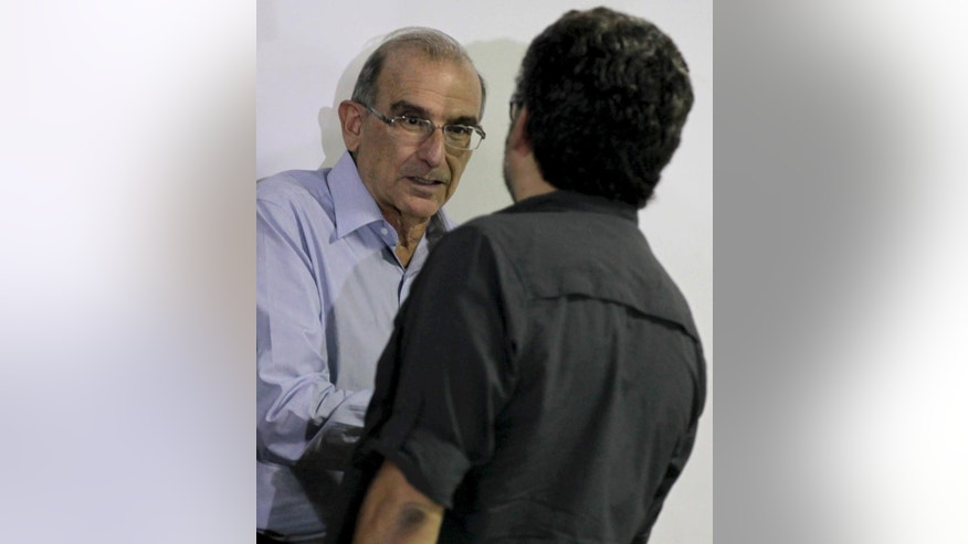 Humberto de la Calle, head of Colombia's government negotiation team, left, speaks with Ivan Marquez, chief negotiator for the Revolutionary Armed Forces of Colombia, or FARC, at the close of another round of peace talks in Havana, Cuba, Saturday, March 7, 2015. Colombia's government and the FARC have agreed to begin a pilot program for removing land mines as part of efforts to lower the intensity of a conflict that has lasted a half century. The announcement came Saturday at the end of the latest round of peace talks being held in Cuba's capital since November 2012. (AP Photo/Ismael Francisco, Cubadebate)