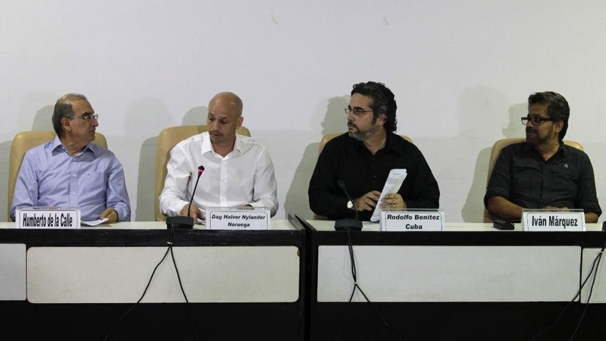 Humberto de la Calle, head of Colombia's government negotiation team, left, and Ivan Marquez, chief negotiator for the Revolutionary Armed Forces of Colombia, or FARC, right, talk during a press conference accompanied by Cuban guarantor Rodolfo Benitez, second from right, and Norwegian guarantor Dag Nylander, second from left, at the close of another round of peace talks in Havana, Cuba, Saturday, March 7, 2015. Colombia's government and the FARC have agreed to begin a pilot program for removing land mines as part of efforts to lower the intensity of a conflict that has lasted a half century. The announcement came Saturday at the end of the latest round of peace talks being held in Cuba's capital since November 2012.  (AP Photo/Ismael Francisco, Cubadebate)