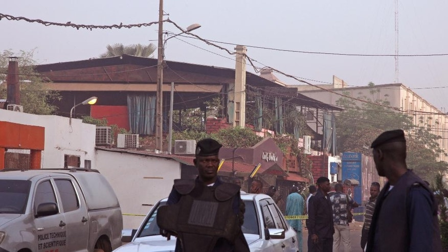 The nightclub, rear, that was attacked by gunmen as Mali police, center, provide security in Bamako, Mali, Saturday, March 7, 2015. At least one masked gunman sprayed bullets in a nightclub popular with foreigners in Mali's capital early Saturday, killing at least five people including a French person and a Belgian national, officials and witnesses said. (AP Photo/Baba Ahmed)